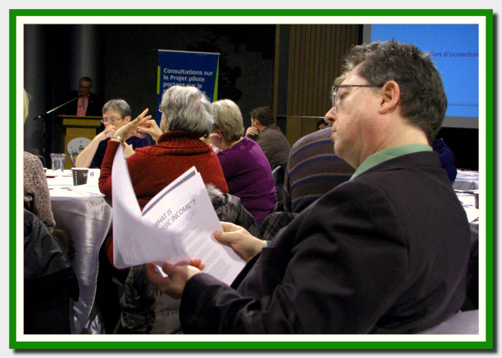 "Bob Jonkman looks over ""What is Basic Income"" handout at the at the Ontario Liberal Party's Waterloo Region Basic Income Consultation"