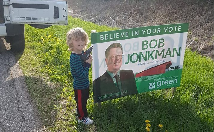 A very young man holds an electric screwgun to put up Bob Jonkman's sign