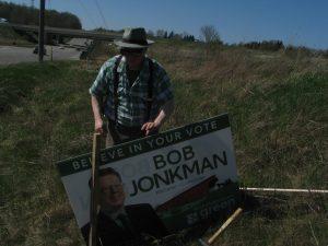 Bob Jonkman puts up an election sign